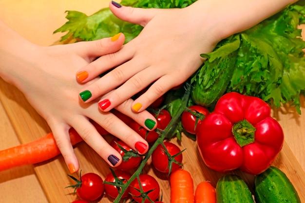Manicure per bambini con smalto colorato per le unghie della ragazza con cibi diversi cetriolo, pomodoro, carota, melanzana.