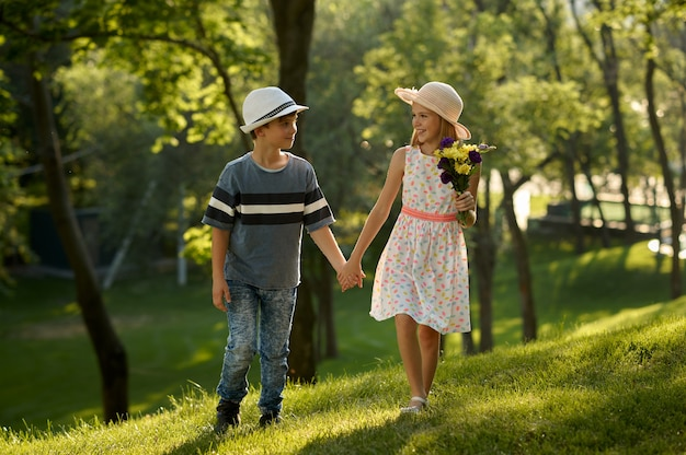Appuntamento romantico per bambini nel parco estivo, amicizia, primo amore. ragazzo e ragazza con bouquet. bambini che si divertono all'aperto, infanzia felice