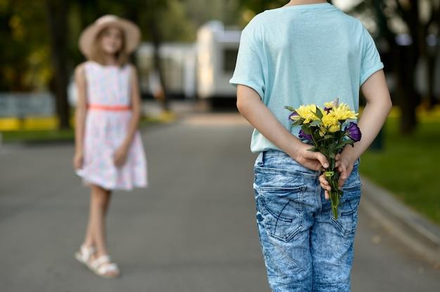 Appuntamento romantico per bambini nel parco estivo, amicizia, primo amore. ragazzo e ragazza con bouquet sul percorso a piedi. bambini che si divertono all'aperto, infanzia felice