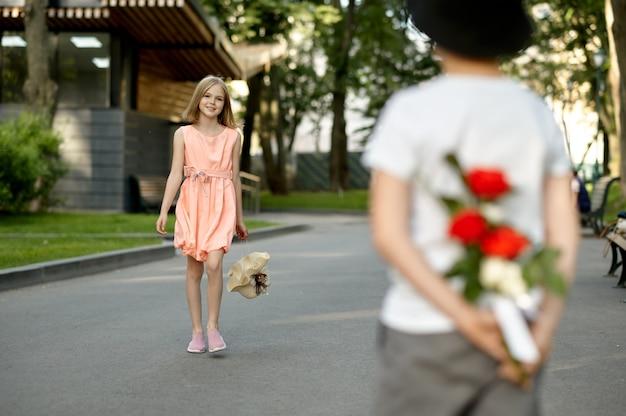 Appuntamento romantico per bambini nel parco estivo, amicizia, primo amore. il ragazzo nasconde i fiori a una ragazza. bambini che si divertono all'aperto, infanzia felice