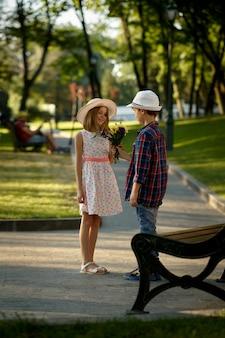 Appuntamento romantico per bambini nel parco estivo, amicizia, primo amore. ragazzo con fiori in attesa di una ragazza in panchina. bambini che si divertono all'aperto, infanzia felice
