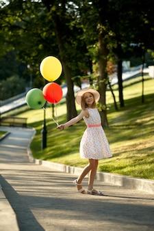 Appuntamento romantico per bambini nel parco estivo, amicizia, primo amore. bambina con gli aerostati. bambini che si divertono all'aperto, infanzia felice