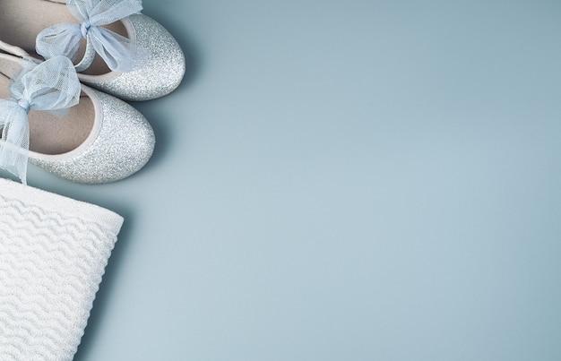 Scarpe e giacca per bambini su sfondo grigio blu.