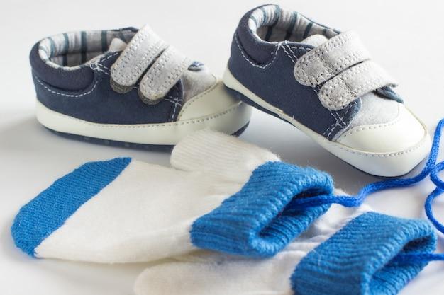 Scarpe e guanti per bambini su uno sfondo bianco
