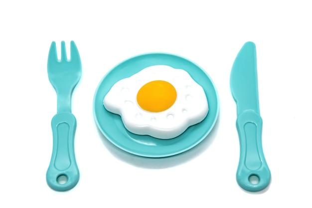 Stoviglie in plastica giocattolo per bambini: piatto con uova fritte, forchetta e coltello