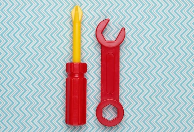 Strumento giocattolo per bambini. chiave inglese, cacciavite su un pastello blu