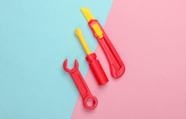 Strumento giocattolo per bambini. chiave inglese, cacciavite, coltello su un pastello blu-rosa