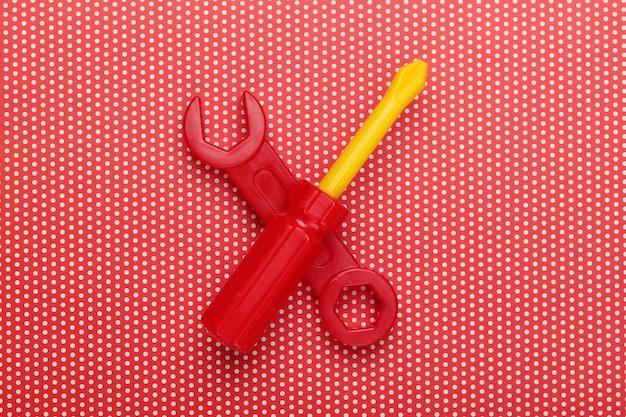 Strumento giocattolo per bambini. chiave inglese, cacciavite su una tovaglia a pois.