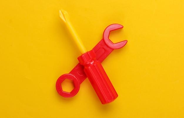 Strumento giocattolo per bambini. chiave inglese, cacciavite su giallo.