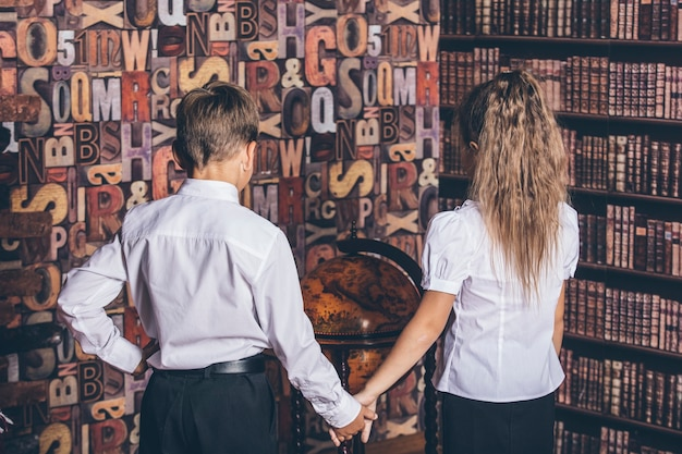 I bambini in età scolare considerano un mappamondo in biblioteca