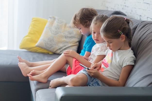 I bambini si siedono sul divano e giocano sul tablet e guardano i cartoni animati