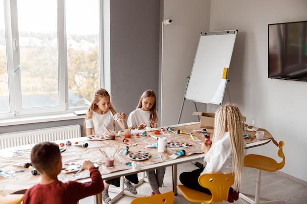 Bambini seduti a tavola che disegnano con entusiasmo con gli acquerelli su carta