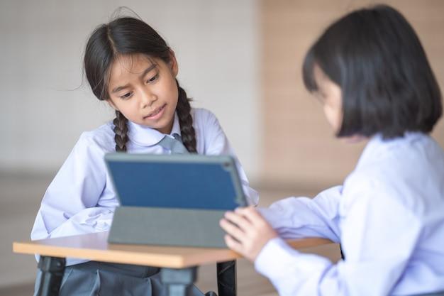 I bambini che tornano a scuola studiano insieme utilizzando la tavoletta digitale e scrivono sul taccuino a scuola