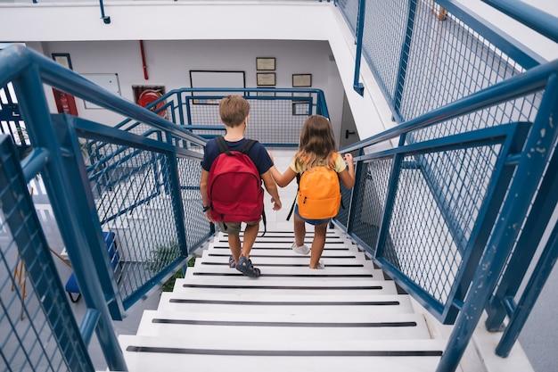Studenti bambini che scendono le scale con le maschere per entrare in classe mantenendo le distanze sociali.