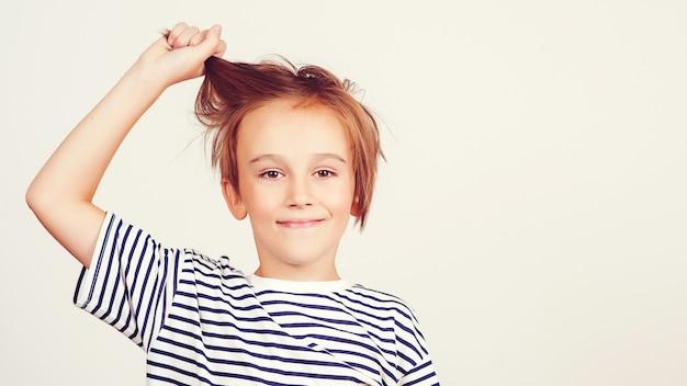 Stile e moda per bambini. ragazzo felice con l'acconciatura alla moda. ritratto di ragazzo divertente. kid divertirsi e ridere. infanzia felice ed emozioni positive. espressione facciale. ragazzo sorridente che propone allo studio.