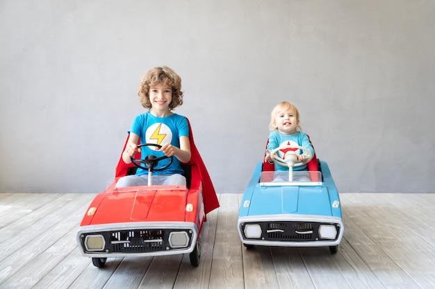 Supereroi dei bambini che giocano in casa