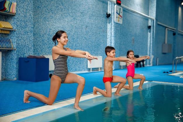 Gruppo di nuoto per bambini, allenamento a bordo piscina.