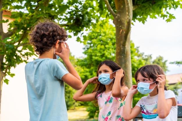 Bambini che si tolgono la mascherina chirurgica seduti su una panchina al parco