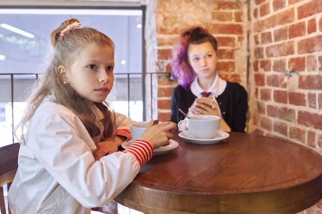Bambini, due sorelle, adolescente e sorella minore, seduti insieme al bar a tavola. ragazze che riposano dopo la scuola