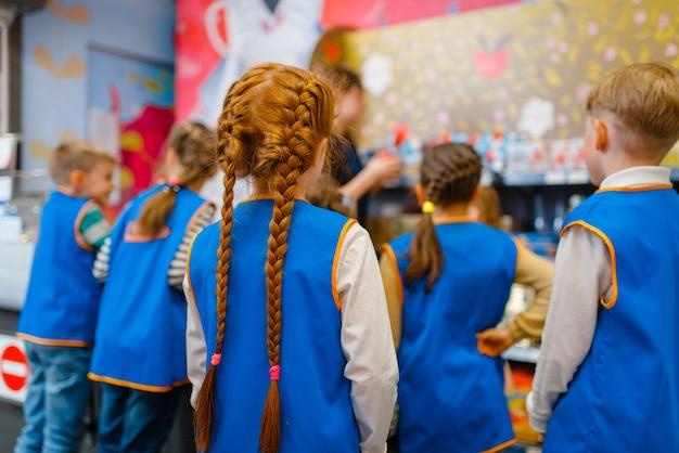Bambini in uniforme che giocano a venditori