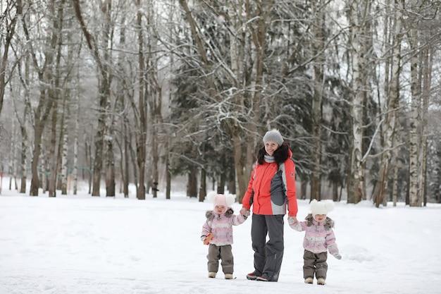 I bambini camminano nel parco in inverno. famiglia della foresta invernale con bambini a passeggio. una fredda giornata invernale è una passeggiata in famiglia.