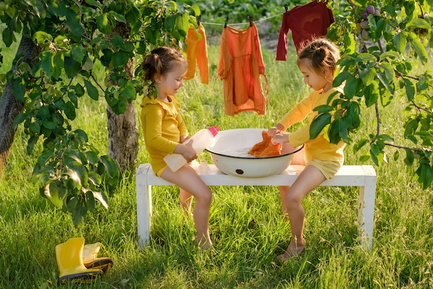 I bambini lavano i vestiti in una bacinella con un gel liquido ipoallergenico per lavare i vestiti dei bambini