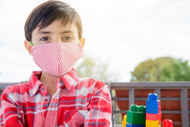 I bambini che indossano la maschera per il viso, i bambini devono indossarla come protezione