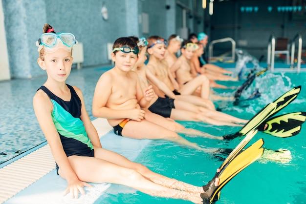 I bambini con le pinne colorate si siede vicino alla piscina