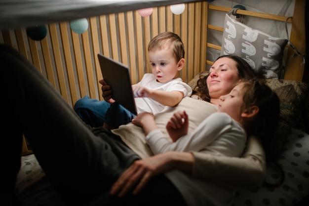 Bambini con la madre che guarda un tablet pc e seduto a letto