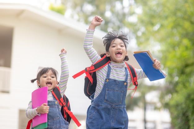 Bambini con zaini che saltano nel parco vicino alla scuola. alunni con libri e zaini all'aperto