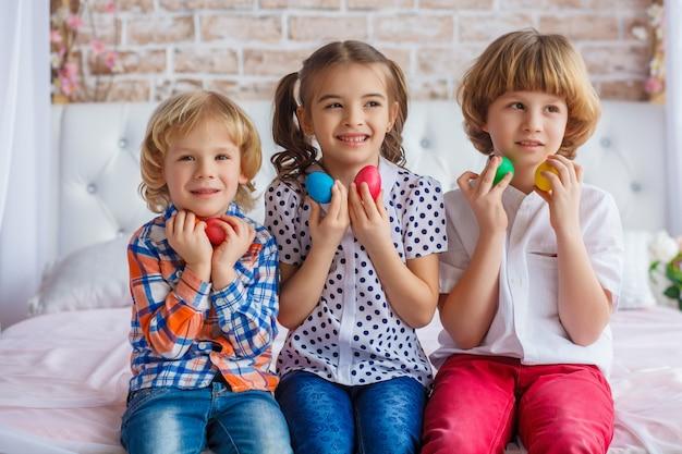 Bambini, una donna e due ragazzi tengono in mano le uova di pasqua. foto divertente. adorabile bambino in abiti colorati, godendo le vacanze