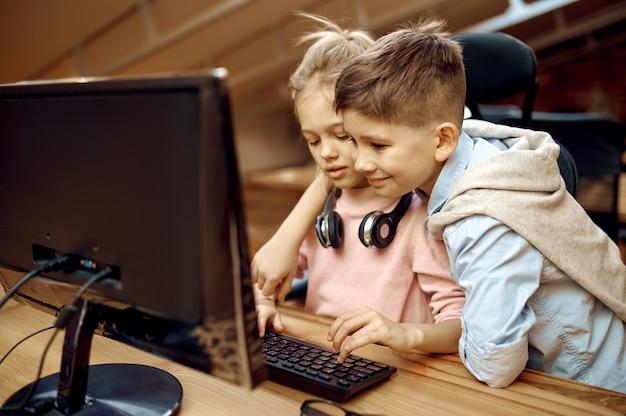 I bambini scrivono commenti sul pc, piccoli blogger. blogging per bambini in home studio, social media per un pubblico giovane, trasmissione internet online, hobby creativo