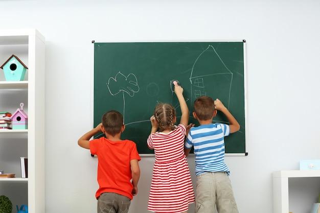 Bambini che scrivono sulla lavagna a scuola