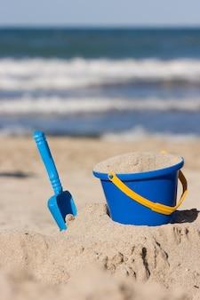 Giocattoli da spiaggia per bambini un secchio e una pala sulla sabbia attività all'aperto per bambini sulla spiaggia