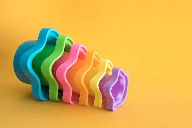 Ciotole di plastica giocattolo colorate per bambini di diverse dimensioni su sfondo giallo