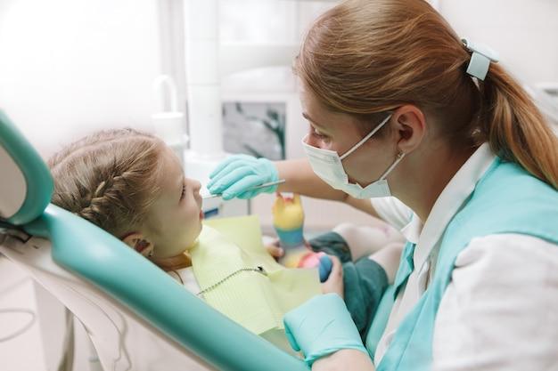 Dentista per bambini che lavora nella sua clinica, esaminando i denti della bambina