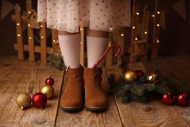I piedi dei bambini con le scarpe marroni lecca-lecca di capodanno con gli stivali