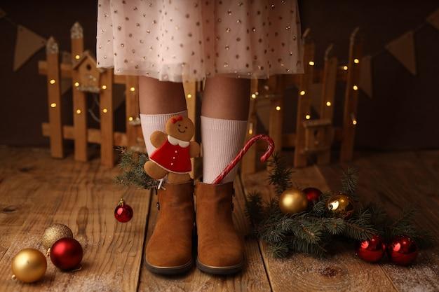 Piedi dei bambini in scarpe marroni lecca-lecca di capodanno e pan di zenzero con gli stivali