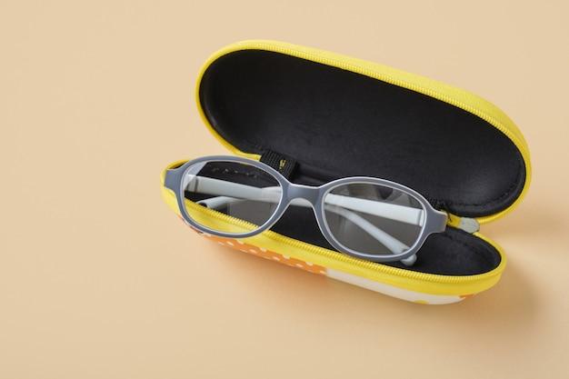 Occhiali per bambini in un caso su sfondo beige