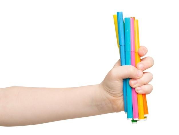 Mano dei bambini che tiene i pennarelli colorati isolati