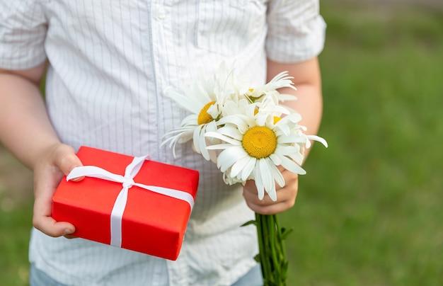 Le mani dei bambini tengono il contenitore di regalo. un concetto della festa della mamma.