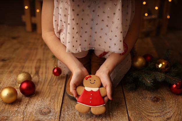 Le mani dei bambini tengono un pan di zenzero di capodanno