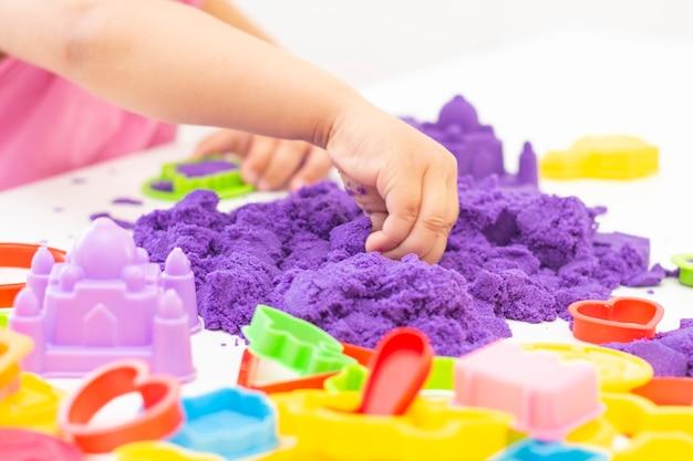 Le mani dei bambini giocano con la sabbia cinetica in quarantena. sabbia viola su un tavolo bianco. pandemia di coronavirus