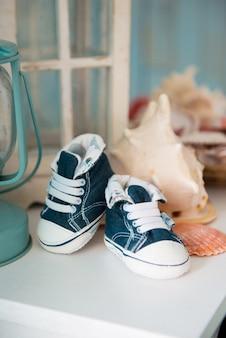 Sneakers jeans per bambini all'interno del mare sullo sfondo di conchiglie