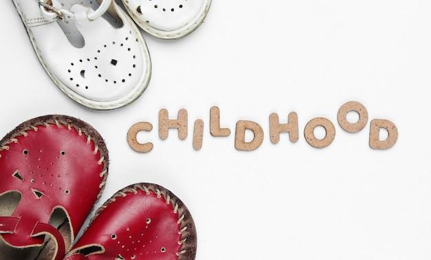 Sandali in pelle per bambini sul blu con la parola infanzia