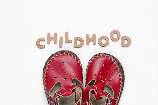Sandali in pelle per bambini su bianco con infanzia di parola