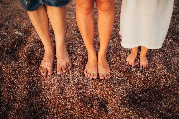 Le gambe dei bambini e i piedi dei genitori la famiglia cammina lungo la spiaggia
