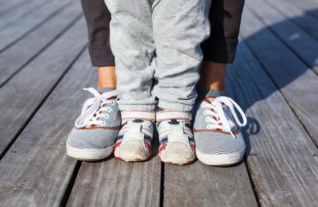 Gambe e piedi dei bambini in scarpe da ginnastica per adulti l'uno con l'altro su fondo di legno