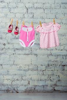 Abito rosa per bambini e scarpe rosse per la ragazza che si asciugano su una corda contro un muro di mattoni bianchi