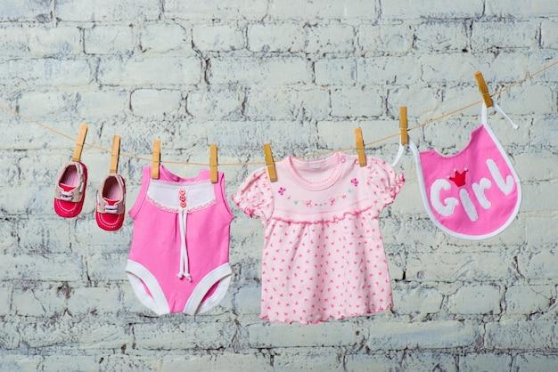 Un bodik rosa per bambini, un bavaglino, un vestito e scarpe rosse per una ragazza asciutta su una corda contro un muro di mattoni bianchi